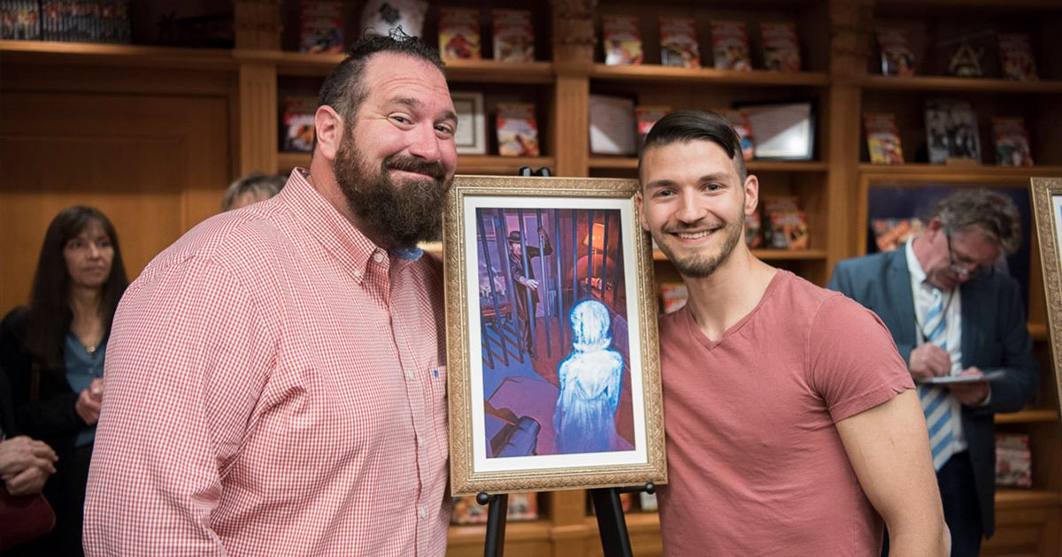 "Jake (L) with artist Ryan Richmond and the illustration for his story ""Acquisition"""