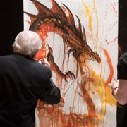 Larry Elmore and Rob Prior painting a dragon on stage