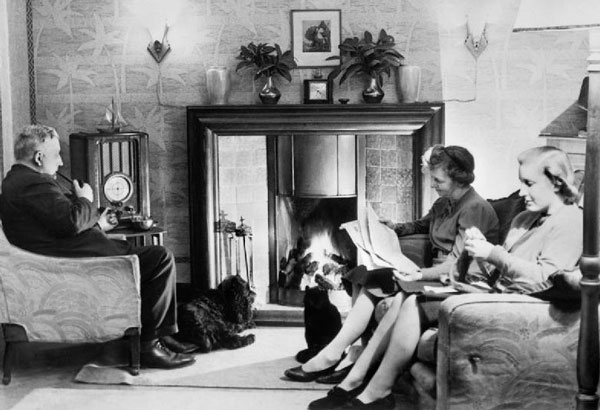 A family relaxes at home listening to a radio program.