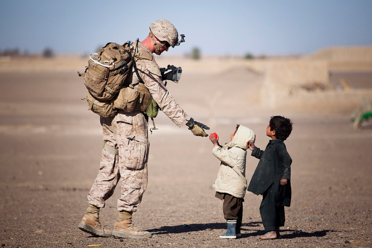 Small child giving soldier a ball