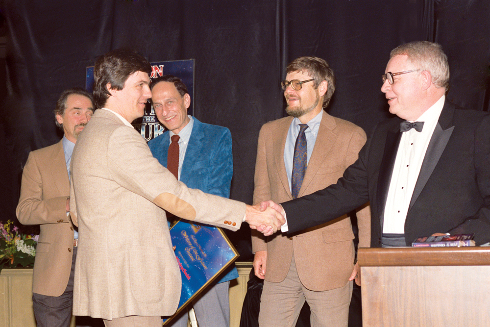 Dean Wesley Smith is congratulated by Algis Budrys with Robert Silverberg, Roger Zelazny and Dr. Gregory Benford looking on.