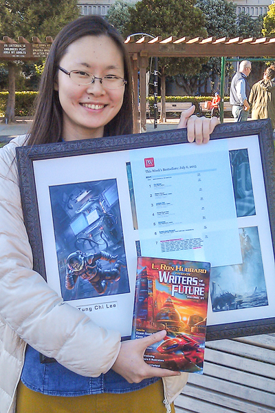 "Jessica with her illustration for ""Unrefined"" by Martin L. Shoemaker in Writers of the Future Vol 31"